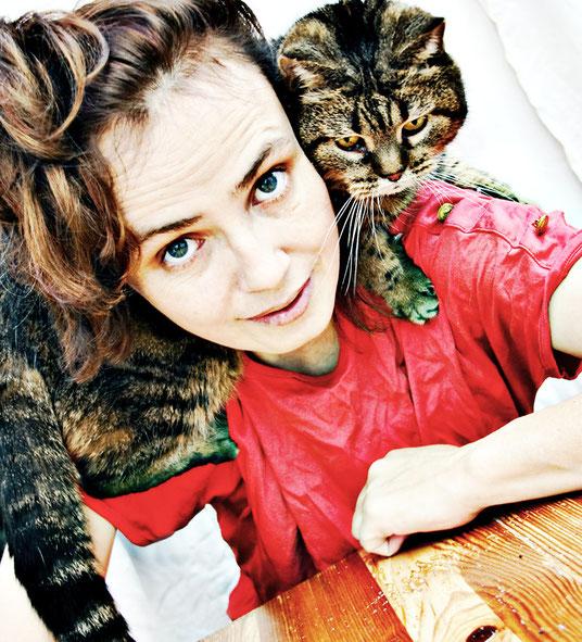Eine Tigerkatze sitzt auf der Schulter einer Frau