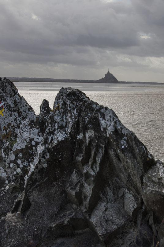 Felsen steigen schroff an der Bucht der Bucht des Mont Saint Michel in der Normandie empor, im Hintergrund der Klosterberg.