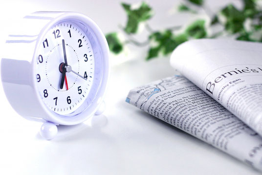 目覚まし時計と新聞。アイビーの葉。
