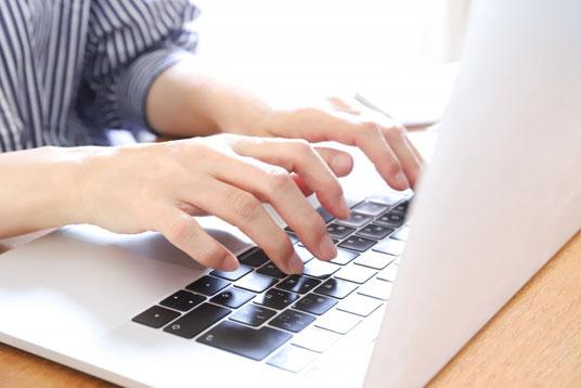 リング式ノートの上に置かれた鉛筆とスマートフォン。ヘッドフォン、コーヒーの入ったマグカップ、ミニサイズの多肉植物の鉢植え。