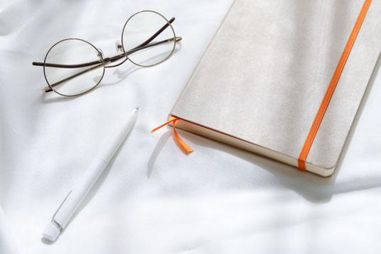 サイト構築。ノートパソコンの画面とスマホ画面を見比べる女性。傍らにマグカップのコーヒー。