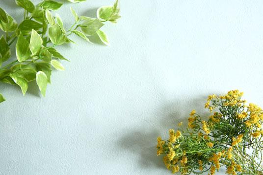 ノートパソコンと広げられた仕事の参考図書。眼鏡、ボールペン、コーヒーの入ったマグカップ。一輪のラベンダーの花。
