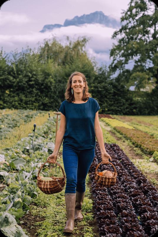 Ariane dans les champs de salades du GAEC bouquet savoyard tenant paniers de légumes