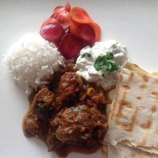 Curry van lamsvlees en aubergine, geserveerd met rijst, platbrood, gekruide yoghurt en zoetzure wortel.