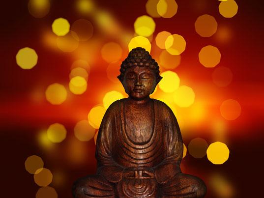 Bouddha en bois qui médite, fond lumineux rouge et jaune.