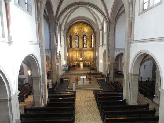 Der Chorraum mit goldenen Gemälden steht im Fokus des Bildes. Vor den braunen Holzkirchenbänken steht der weiße quadratische Altar.