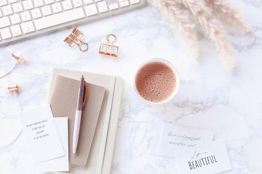 木目調のデスクに広げられたノートパソコン。そのうえに置かれたべっ甲フレームの眼鏡。バインダーと定規、ボールペン。ピンクのスイトピー。