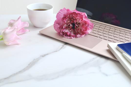 ノートパソコン。コーヒーの入ったピンクのカップ&ソーサ。リングノートの上に置かれた腕時計。