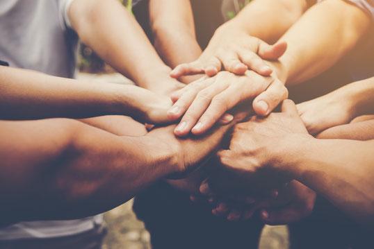 社員に向けた経営計画書・事業計画書を発表し団結しているイメージ