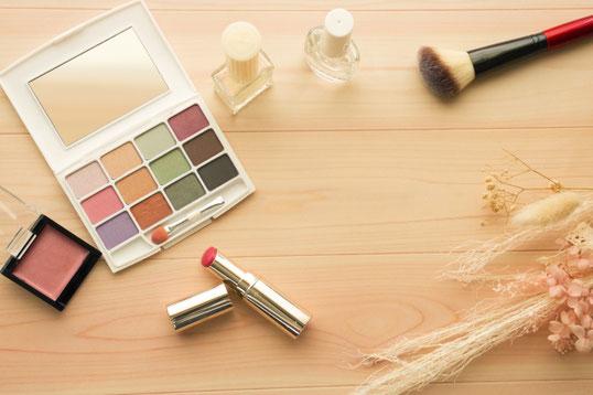 濃いピンクのラナンキュラスの花。デスクに広げられたノートとボールペン。マニキュアの小瓶。