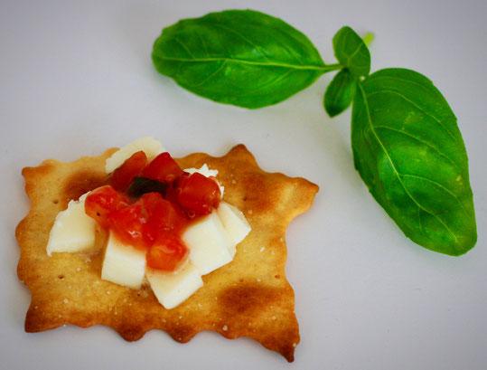Cracker mit Mozzarella Würfel und Tomaten Basilikum Relish