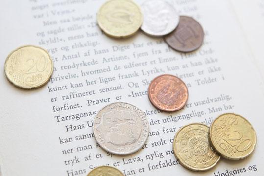 住宅の設計図。建設中の住宅のミニチュア。積まれた銀のコイン。退職金で家を建てる。