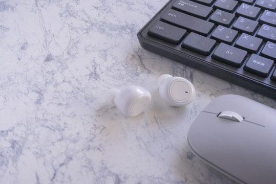 デスクに広げられたコピー用紙。マウス、眼鏡、ボールペン、鉛筆。コーヒーの入った赤のマグカップ。