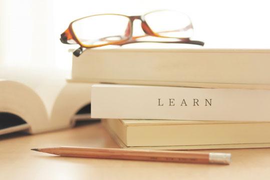 積まれたテキストの上に置かれた眼鏡。鉛筆。