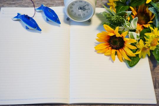 マーブル調のデスクに置かれた分厚いスケジュール帳とボールペン。傍らにひまわりが活けられたガラスの花びん、キャンドル、コーヒーの入ったマグカップ。