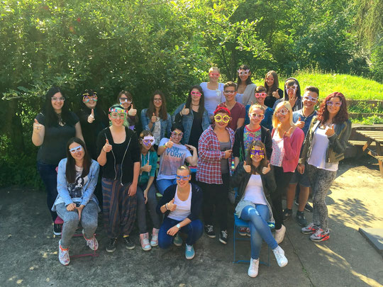 """Sie posieren mit ihren ersten selbst entworfenen Brillengestellen (Fach PGID) im Schulgarten und wünschen allen """"Neuen"""" einen guten Start! Diese 20 Mädchen und drei Jungen machen eine Berufsausbildung mit Fachabitur."""