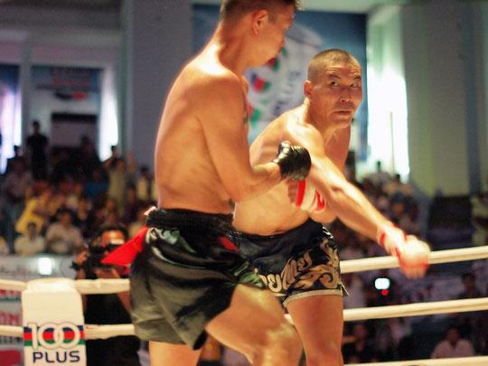 Im Boxring sind zwei asiatische Boxer, die Lethwei kämpfen. Sie haben nur Thaiboxhosen an und bandagierte Fäuste.