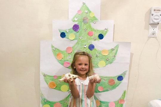 Kind vor dem aufgemalten Tannenbaum