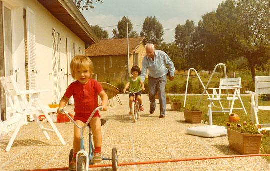 Roland aide  Alexandra à rouler sans petites-roues, Boris file en tricycle