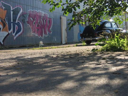 Aufnahme: Leicht verdeckter Oldtimer hinter Blättern bzw. Grünwerk