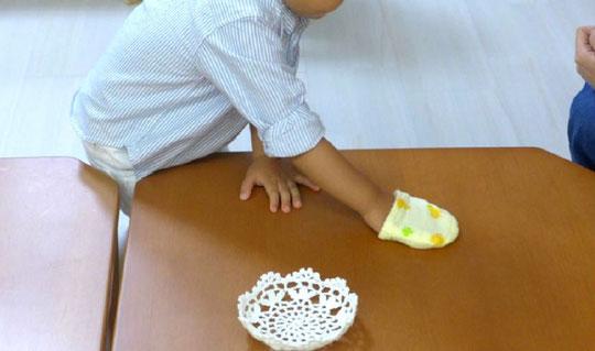 モンテッソーリ教育の「日常生活の練習」活動として、ステッラコースの1歳児が専用の用具で机拭きに取り組んでいます