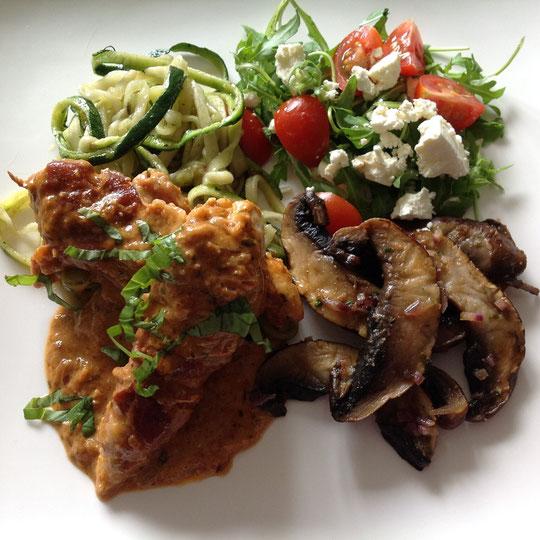 Kip met zongedroogde tomaten pesto roomsaus geserveerd met courgette, paddestoelen en salade.
