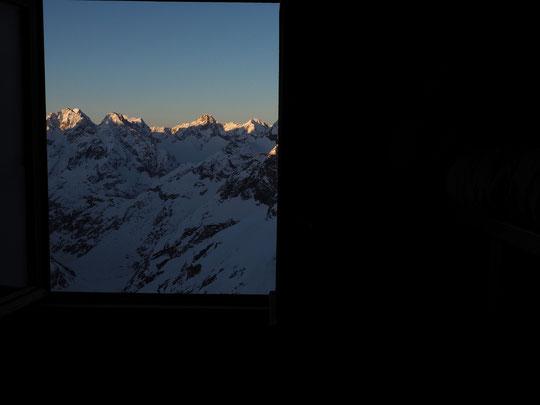 Fenêtre ouverte, sur l'Oisans. Au réveil depuis le dortoir du Promontoire. Le soleil coiffe juste (de gauche à droite) la cime de l'Encoula, la Grande Aiguille de la Bérarde, les Rouies (au fond), la Tête de l'Etret ainsi que la tête des Fétoules.
