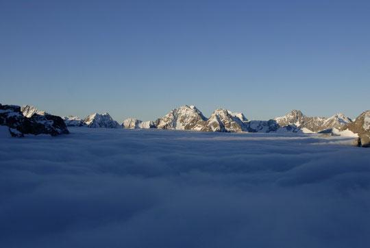 Depuis la terrasse du refuge, soleil matinal et plafond nuageux vers les 3000 m.