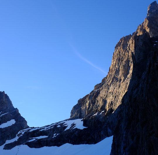 """La brèche de la Meije (3350m) avec un enneigement très faible pour une mi juin et la facette Sud Ouest ( avec plusieurs voies dont """"Nous partirons dans l'Ivresse""""), avec la lumière du soir."""