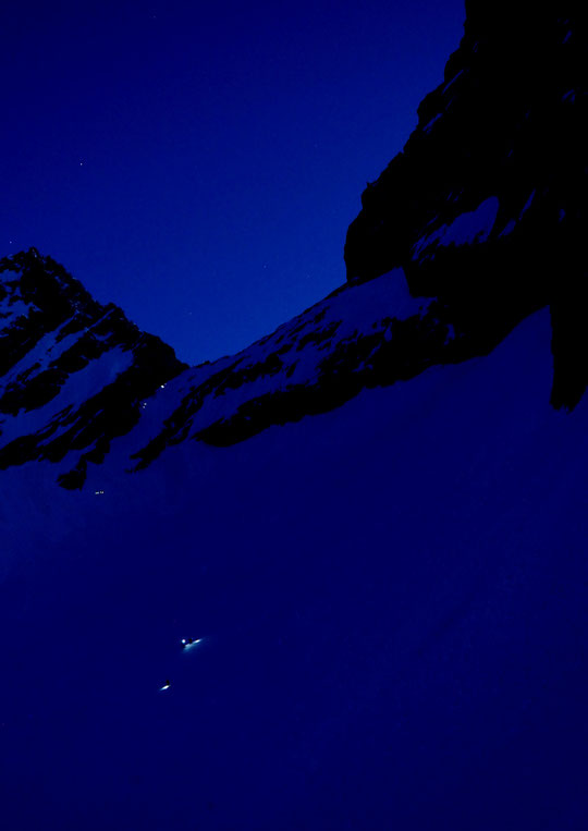 Quand le jour se lève, le ciel au dessus de la brèche de la Meije est encore parsemé des étoiles de la nuit.  Au sol entre 3200 et 3400m,  les skieurs qui ont passé la nuit au refuge montent à leur rencontre....