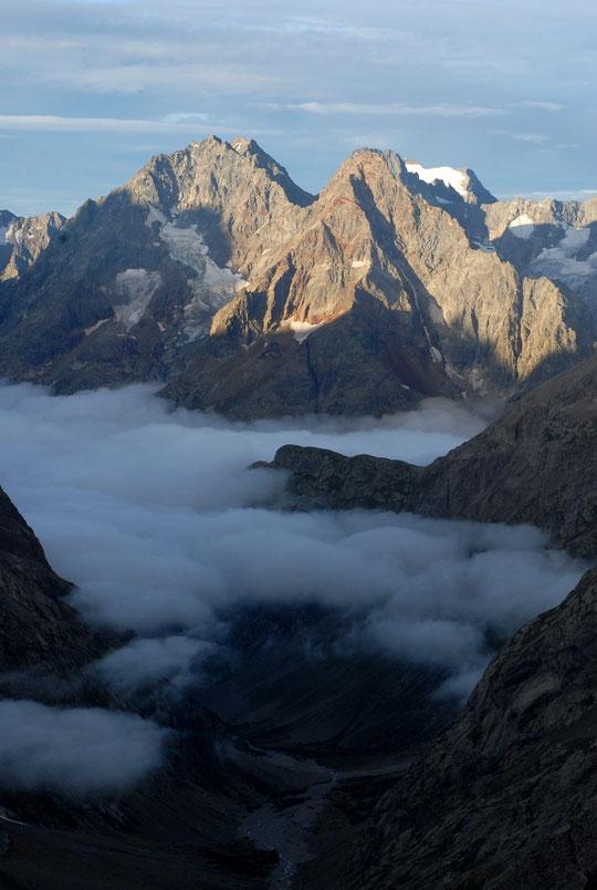 Un matin, depuis la terrasse du refuge : en bas le vallon des Etançons, une petite mer de nuages au dessus de la Bérarde, la tête de la Maye (2500m) qui sort juste des nuages, la Grande Aiguille de la Bérarde et au fond le sommet des Rouies (Valgaudemar).