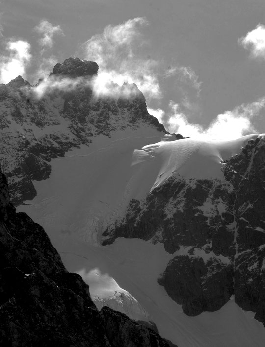 Depuis la terrasse du refuge du Promontoire : de petits nuages jouent avec le soleil autour du sommet du Pavé (3735m) et au dessus du col du Pavé (3550m), plutôt en bonnes conditions. (photo prise dimanche matin)