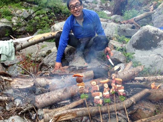 串焼きもたき火で料理します。 撮影:H瀬さん