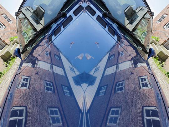 Bild: verdoppelte Spiegelung eines Hauses in einer Autoscheibe.