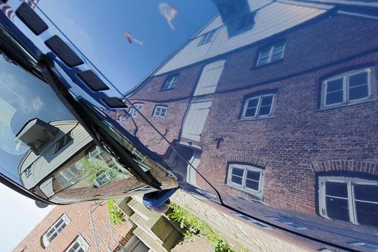 Bild: in der Autoscheibe gespiegeltes Haus