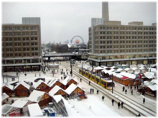 Bilder vom Alexanderplatz in Berlin mit der neuen gelben Tram und einem Weihnachtsmarkt. Im Hintergrund sieht man ein Riesenrad des Weihnachts-Rummels.