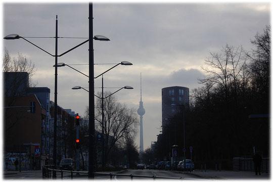 Auf dem Foto sieht man den Fernsehturm in Berlin vom Bezirk Wedding aus. Das Bild wurde im Herbst aufgenommen, der Fernsehturm liegt in einer trüben Wolkenmasse.
