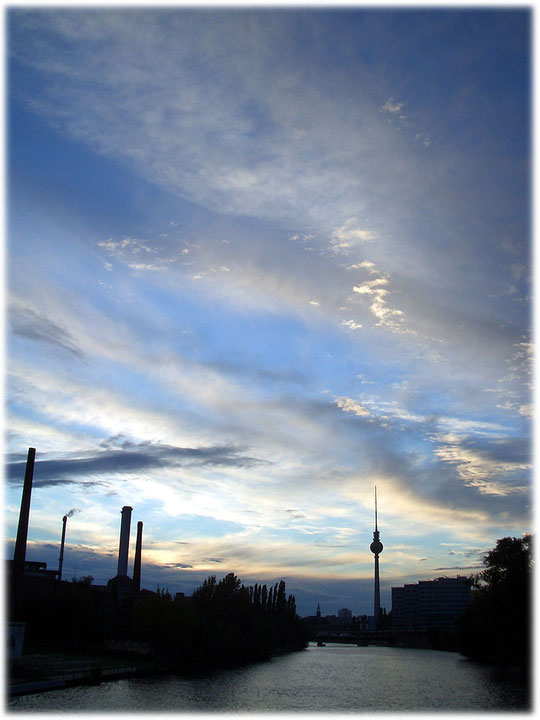 Der Berliner Fernsehturm in Fotos und Bildern. Auf diesem Foto ist der Turm von Treptow aus zu erkennen. das Bild zeigt die Abenddämmerung, im Vordergrund führt die Oberbaumbrücke über die Spree.
