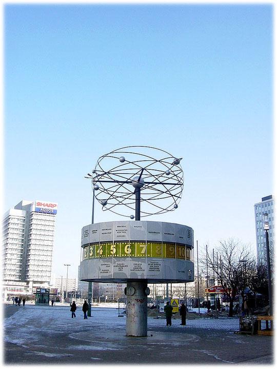 Ein Bild von der DDR Weltzeituhr am Alexanderplatz in Berlin Mitte. Das Foto ist aus dem Jahr 2006 und man sieht noch deutlich die Begrünung des Alexanderplatzes im Hintergrund.