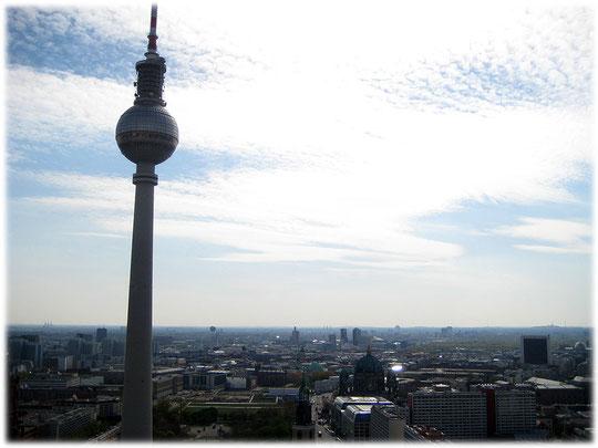 Das Bild vom Berliner Fernsehturm zeigt die Kuppel und den Turm des Fernsehturms. Unter dem Turm ist die Mitte von Berlin deutlich erkennbar. Bilder und Fotos vom Fernsehturm in Berlin.