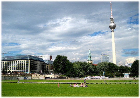 Ein Foto von der Wiese, auf der früher der Palast der Republik stand. Auf dem Foto ist im Hintergrund der Fernsehturm zu sehen, daneben das Park Inn Hotel am Alexanderplatz und die Marienkirche.