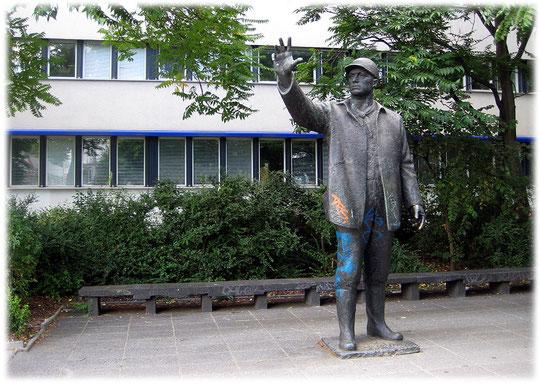 Bild von einem sozialistischen Genossen in Stein und Metall. Auf dem Foto sieht man deutlich, wie der Genosse seine kommunistischen Freunde grüßt.