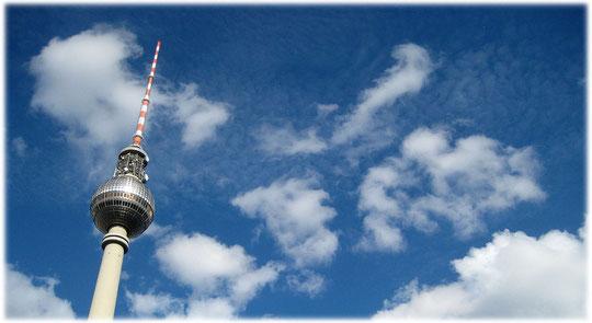 Das Foto zeigt den Berliner Fernsehturm am Alexanderplatz. Der Turm auf dem Bild scheint die Wolken schon zu berühren. Bilder vom Fernsehturm am Alexanderplatz, dem Herzen der DDR und von Ostberlin!