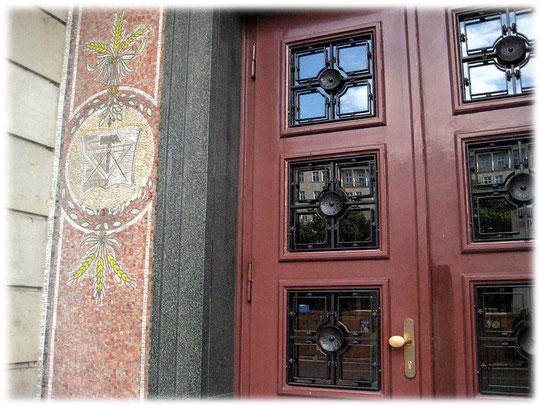Bild einer Eingangstür an der Karl-Marx-Allee im Berliner Bezirk Friedrichshain. Auf dem Bild sieht man die Symbole des Kommunismus und des Sozialismus in der DDR.