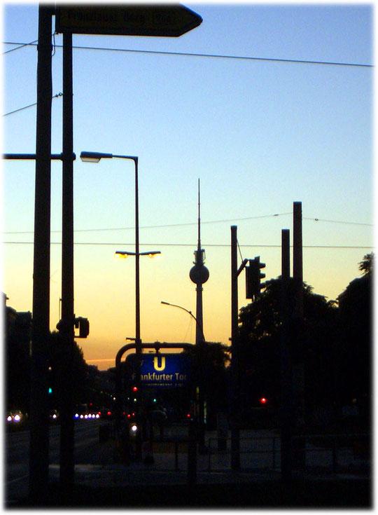 Ein Bild vom Fernsehturm, vom Bezirk Friedrichshain aus fotografiert. Auf dem Foto ist eine Abendstimmung zu sehen, die den Turm in ein schönes warmes Licht taucht. Karl-Marx- und Frankfurter Allee
