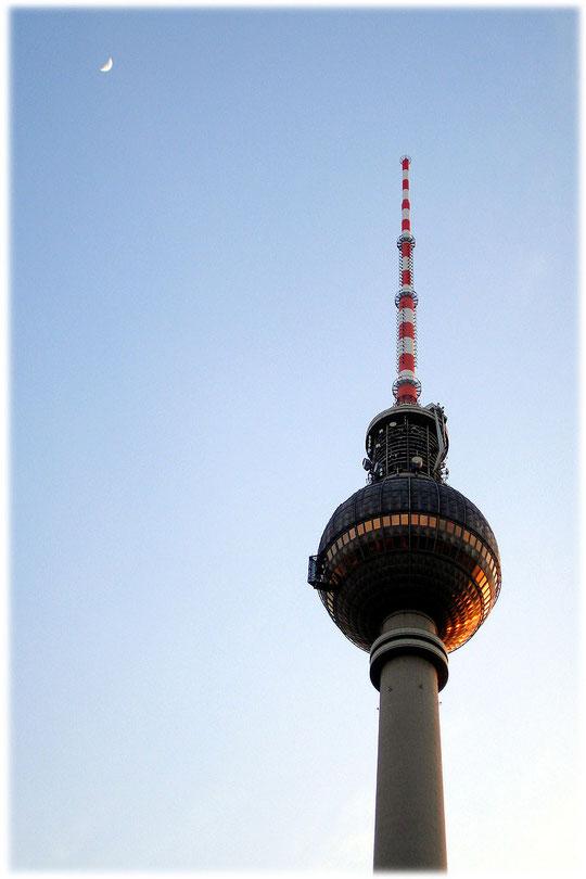 Foto vom Fernsehturm Berlin mit Abendstimmung. Der Mond ist auf dem Bild deutlich sichtbar. Bilder und Fotos aus der DDR und dem ehemaligen Herzen von Ost-Berlin. Bilderbuch Berlin