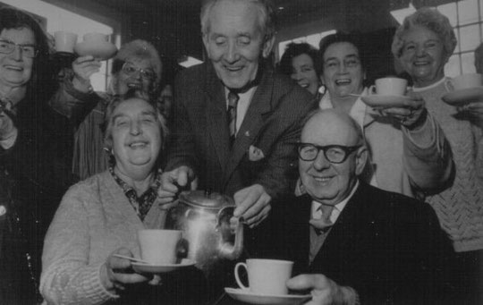The 100,000th cup is celebrated, February 1987. In the centre is Arthur Williams, leading light of the Coffee Morning, and the couple in front are Miriam and Frederick Bates.