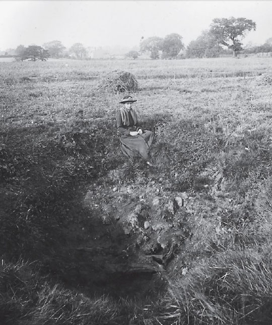 A lady sits by a bomb crater at Lakey Lane, caused by a Zeppelin raid