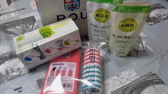 Des cadeaux pratiques pour la maison: une petite balayette, 2 recharges de gel douche, 1 pochette et 2 serviettes