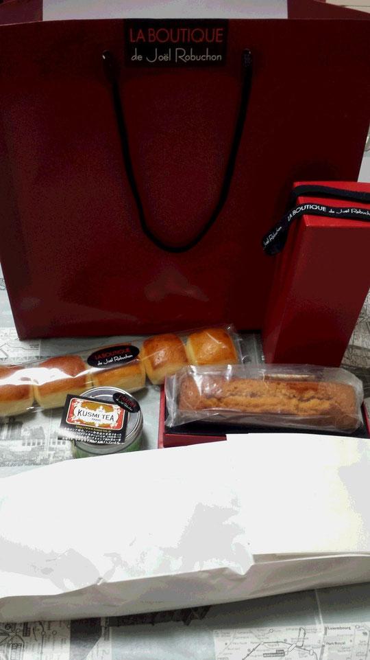 Une avalanche de produits de la Boutique de Joël Robuchon: du thé, un gâteau au caramel, une baguette et des petits pains au lait.
